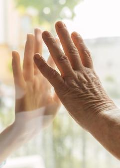Ältere frau, die während der pandemie hand mit jemandem durch fenster berührt