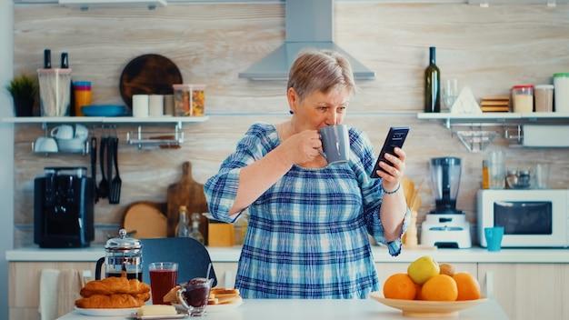 Ältere frau, die während des frühstücks in der küche mit einer tasse kaffee musik vom smartphone genießt. entspannter seniorentanz, lustiger lebensstil mit moderner technologie