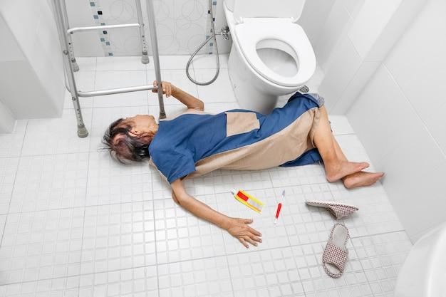 Ältere frau, die wegen rutschiger oberflächen ins badezimmer fällt