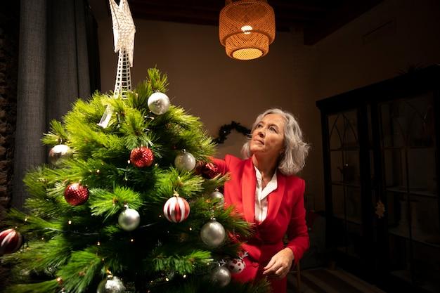 Ältere frau, die weihnachtsbaum gründet