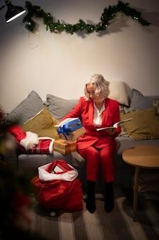 Ältere frau, die weihnachtsgeschenke gründet