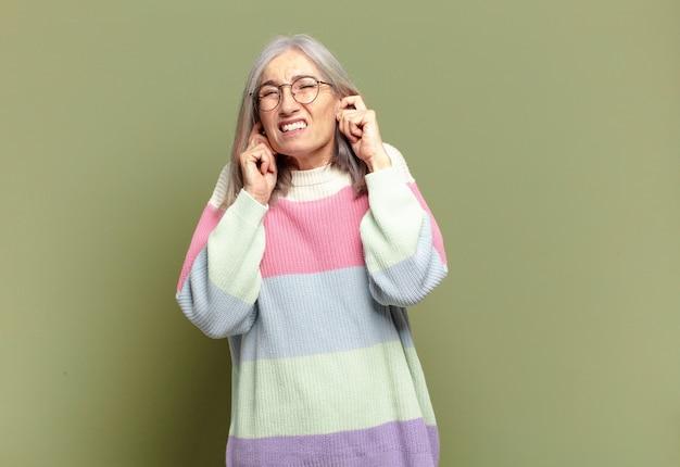 Ältere frau, die wütend, gestresst und genervt aussieht und beide ohren mit einem ohrenbetäubenden geräusch, geräusch oder lauter musik bedeckt