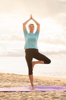 Ältere frau, die yoga am strand praktiziert