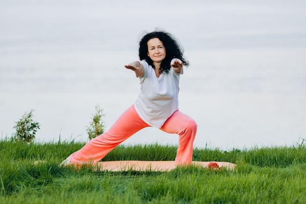 Ältere frau, die yoga asana mit den geraden händen im freien und dem schauen tut. vorderansicht