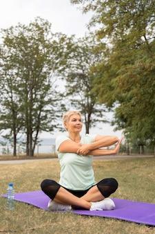 Ältere frau, die yoga draußen im park praktiziert