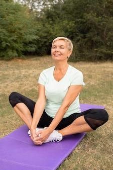 Ältere frau, die yoga draußen im park tut