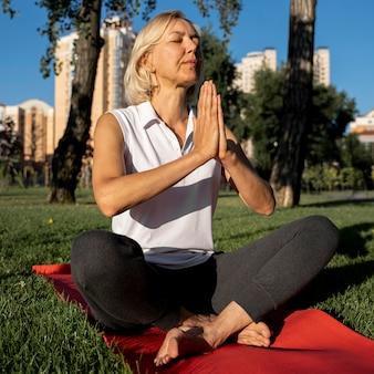 Ältere frau, die yoga im freien praktiziert