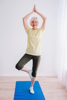 Ältere frau, die yoga im innenbereich macht, anti-age-sport-yoga-konzept