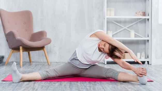 Ältere frau, die yoga im wohnzimmer ausdehnend tut