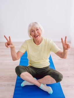 Ältere frau, die yoga online macht, indoor-anti-age-sport-yoga-konzept