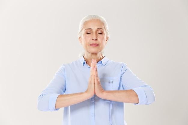 Ältere frau, die yoga praktiziert, hände in namaste hält und ihre augen geschlossen hält