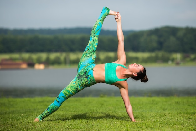 Ältere frau, die yogaübungen mit bergen dahinter macht