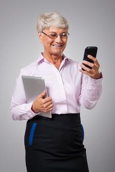 Ältere frau, die zeitgenössische technologie in ihrem geschäft verwendet