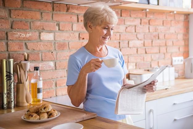 Ältere frau, die zeitung in der küche liest