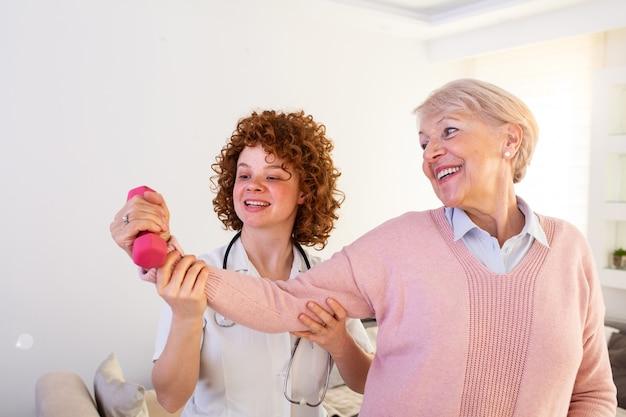 Ältere frau, die zu guter gesundheit zurückkehrt. physiotherapeutin krankenschwester hilft einer älteren frau körperliche rehabilitation