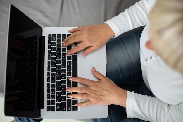 Ältere frau, die zu hause an einem online-kurs auf ihrem laptop teilnimmt