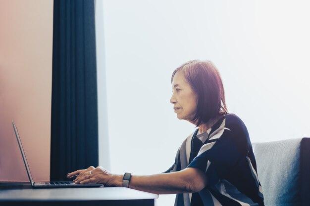 Ältere frau, die zu hause an laptop-computer arbeitet