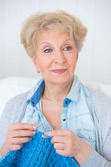 Ältere frau, die zu hause auf ihrem sofa strickt