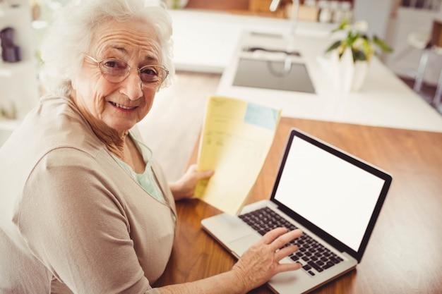 Ältere frau, die zu hause auf laptop schreibt