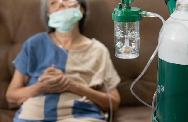 Ältere frau, die zu hause eine sauerstoff-nasenkanüle trägt.