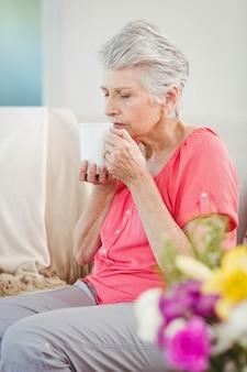 Ältere frau, die zu hause einen tasse kaffee riecht