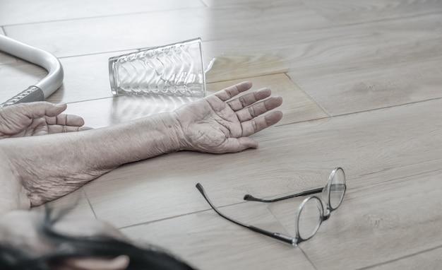 Ältere frau, die zu hause herunterfällt, herzinfarkt.