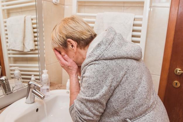 Ältere frau, die zu hause ihr gesicht wäscht