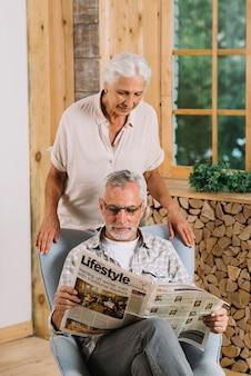 Ältere frau, die zu hause ihre ehemannlesezeitung betrachtet