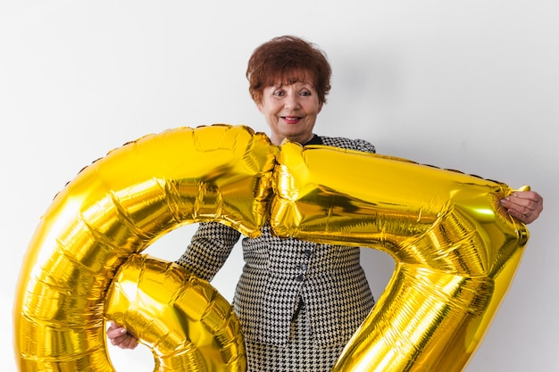 Ältere frau, die zu hause ihren birthay mit kuchen, ballons und konfetti feiert