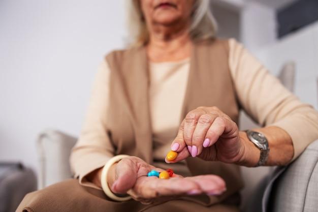 Ältere frau, die zu hause in ihrem stuhl sitzt und hand voll von pillen und vitaminen hält. selektiver fokus zur hand.