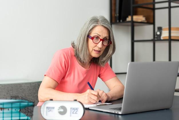 Ältere frau, die zu hause lernt, während sie den laptop benutzt und notizen macht