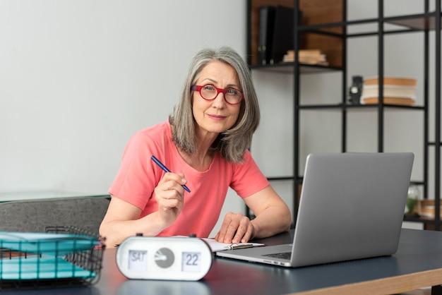 Ältere frau, die zu hause lernt, während sie den laptop benutzt und notizen macht Premium Fotos