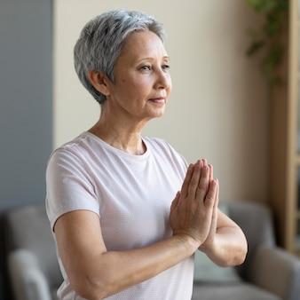 Ältere frau, die zu hause meditiert