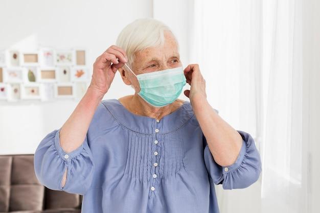 Ältere frau, die zu hause medizinische maske trägt