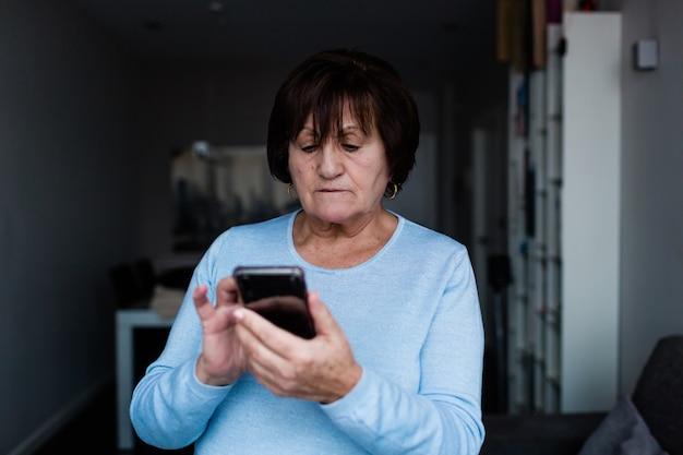 Ältere frau, die zu hause steht und mit einem mobiltelefon plaudert