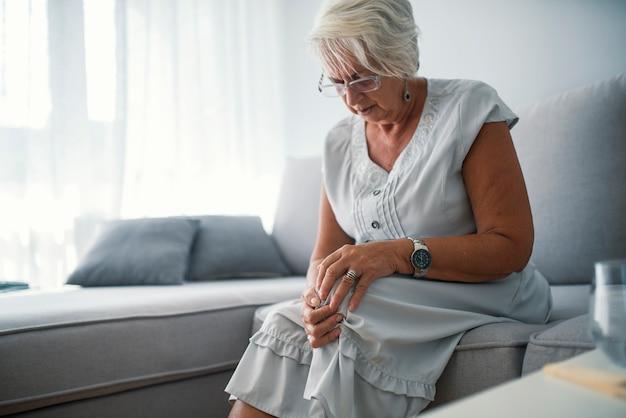 Ältere frau, die zu hause unter den schmerz im knie leidet