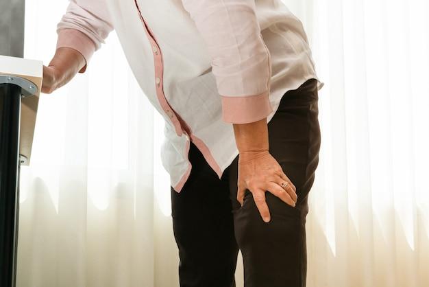 Ältere frau, die zu hause unter knieschmerz, gesundheitsproblemkonzept leidet