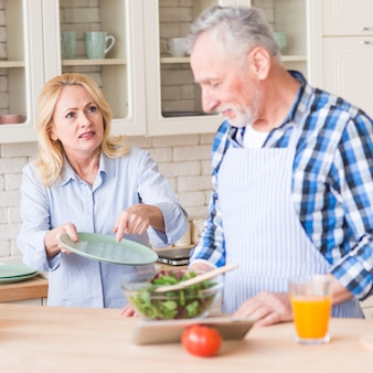 Ältere frau, die zu ihrem ehemann für das säubern der platte schreit