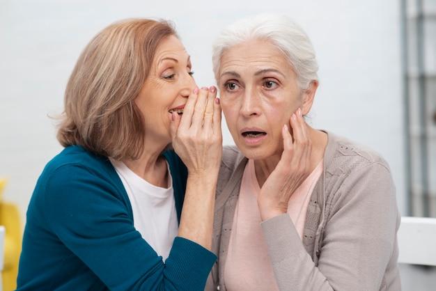 Ältere frau, die zu ihrem freund flüstert