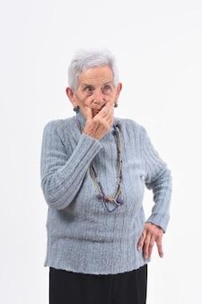 Ältere frau, die zweifel und fragen über weißen hintergrund hat
