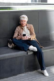Ältere frau draußen in der stadt, die auf einer bank sitzt und smartphone benutzt