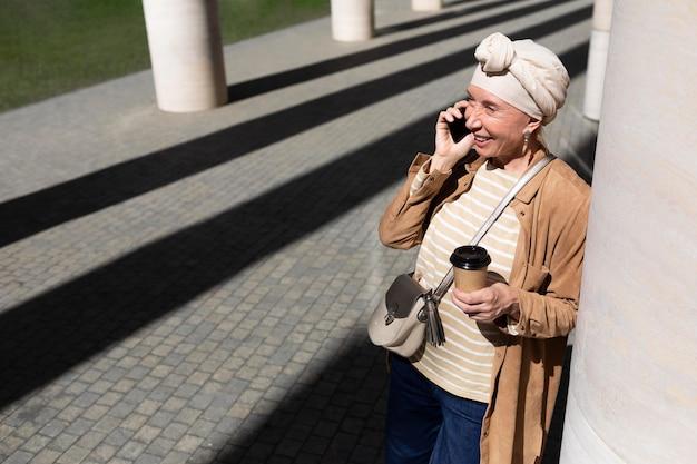 Ältere frau draußen in der stadt, die beim kaffee telefonieren
