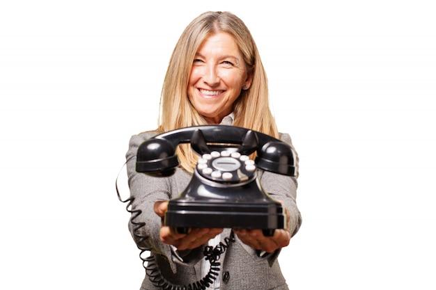 Ältere frau, ein altes telefon in die hand