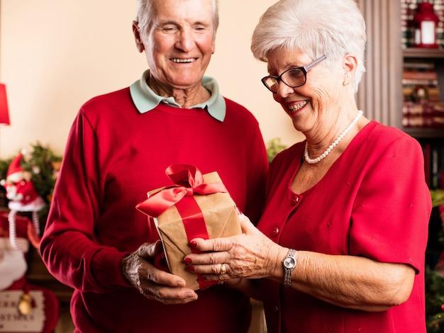 Ältere frau, ein geschenk zu ihrem mann geben