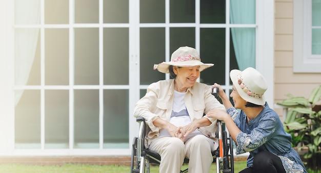 Ältere frau entspannen auf rollstuhl im hinterhof mit tochter