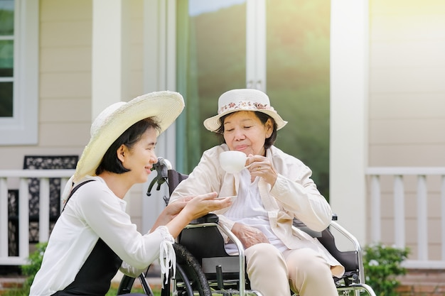 Ältere frau entspannt sich mit tochter im rollstuhl im hinterhof