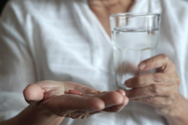 Ältere frau essen medizin und mit pillen und glas wasser zu hause