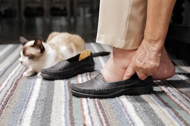 Ältere frau geschwollene füße, die schuhe anziehen