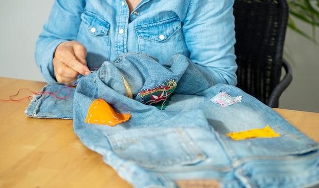 Ältere frau hände nähen auf einem stoff jeans