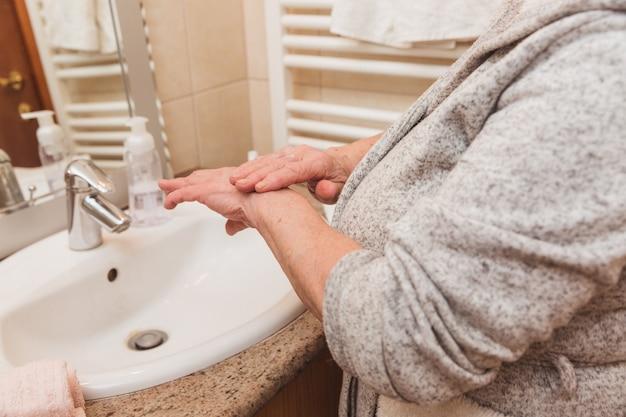 Ältere frau im bademantel, der handcreme im badezimmer aufträgt